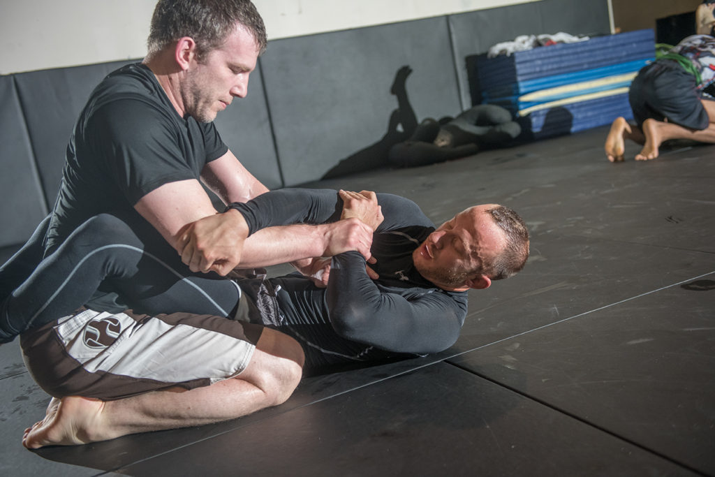 two Brazilian Jiu-Jitsu fighters grappling at a training session.
